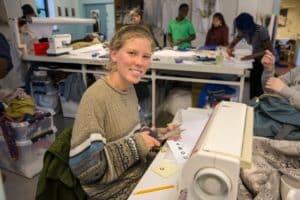 Lerke i tekstil lokalet ved symaskinen